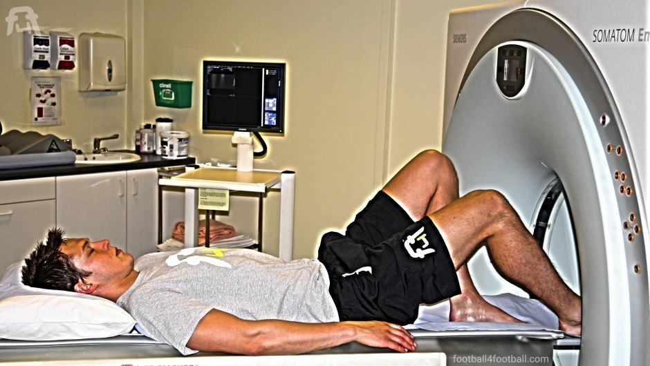 A footballer prepares to have his in injured ankle area scanned.