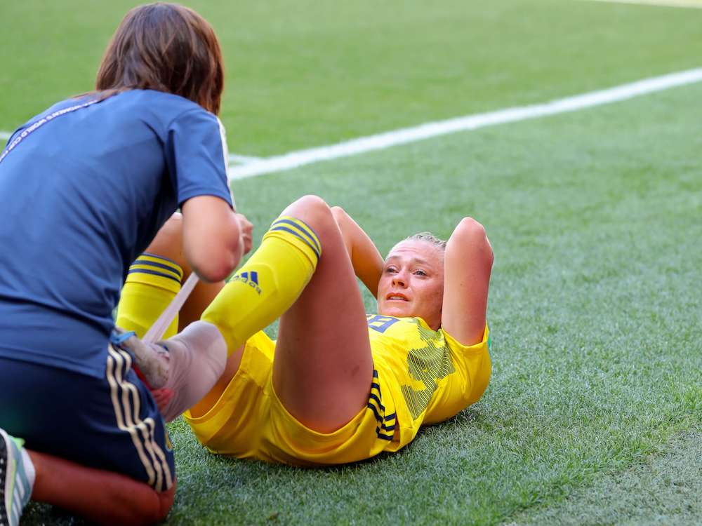 an_injured_female_footballer_recieves_treatment_from_physiotherapist