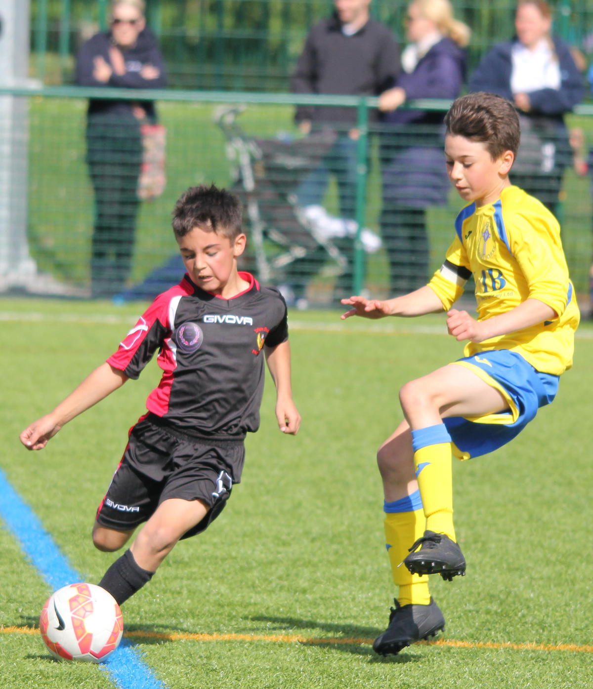 A_young_player_runs_past_an_opponent_during_a_football_game_football4football