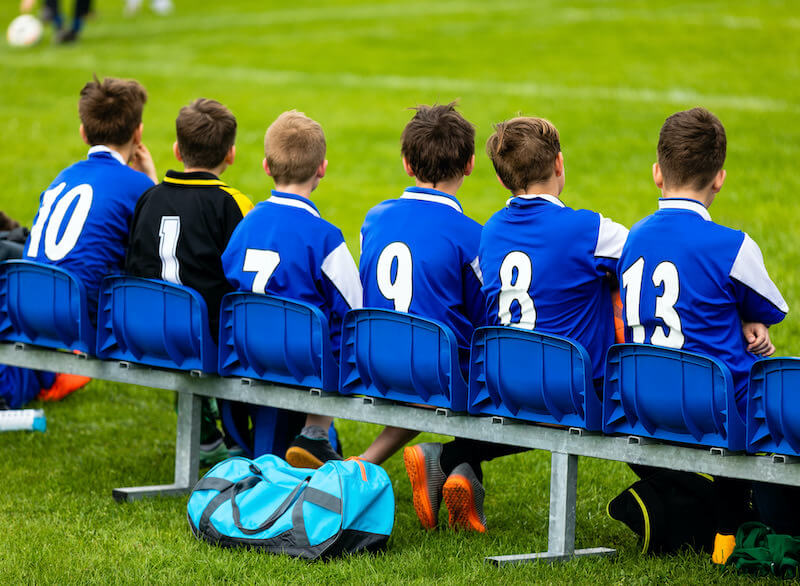 Players_sit_on_the_bench_waiting-to-play-a-football-match-football4football
