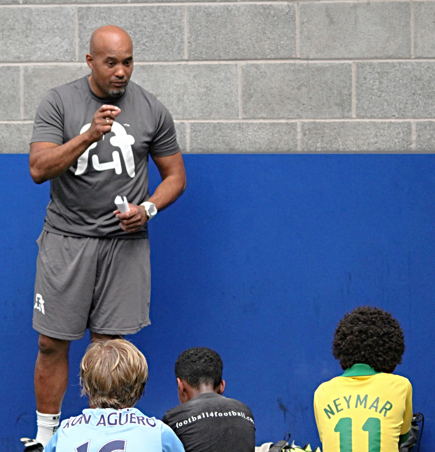 A_coach_gives_instructions_to_a_group_of_young_footballers_at_training
