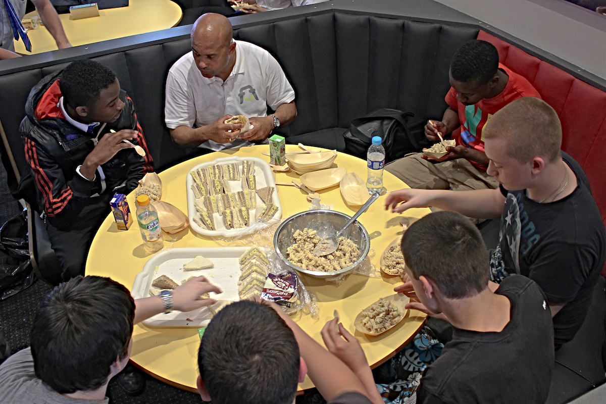 A_coach_eats_with_some_young_players_after_football_training_football4football